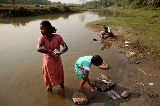 Chandana Barman, 14, bathes with a friend near the rural village of Nakarkhana, India. Many homes in this part of rural West Bengal lack electricity and running water. However, families prize the security of owning their land and having it in a good location. (Erika Schultz/Seattle Times/MCT)