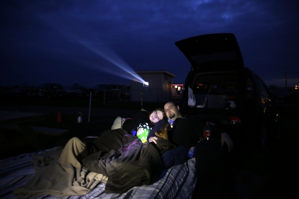 Heidi Mules and Gary Katzer watch a documentary about the history of drive-ins with their Chiweenie named Trixie on a queen-size airbed and couch set up behind their car at the Harvest Moon Twin Drive In Movie Theatre in Gibson City, Illinois, April 28, 2013. (Michael Tercha/Chicago Tribune/MCT)