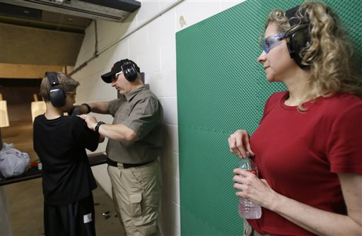 In this Sunday, May 19, 2013, photo, Cheryl Strain, right, watches as instructor Scott Stevens, center, shows her son Rory, 12, how to properly hold a shotgun at a shooting range in Houston. The Strains live in the first residential area being trained and equipped by a nonprofit that is giving away free shotguns to single women and neighborhoods with high crime rates. (AP Photo/Pat Sullivan)