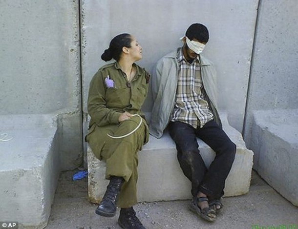 An Israeli soldier posing with a blindfolded Palestinian prisoner in 2010
