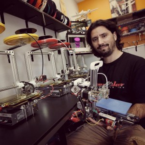 Diego Porqueras holds a Bukito 3-D printer as Bukobot 3-D printers sit on the counter to the left made by Deezmaker in his newly opened Deezmaker store in a strip mall in Pasadena, California, July 25, 2013. (Anne Cusack/Los Angeles Times/MCT)